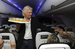 Richard Branson serving customers on a Virgin flight